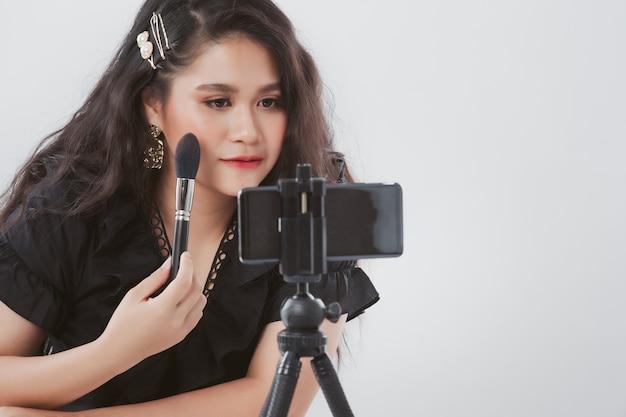 スタジオで白で三脚にスマートフォンで動画を録画し、彼女の美容ブログにアドバイスを与えながら化粧品を見せているアジアの女性の肖像画。美容ブロガーのコンセプトです。