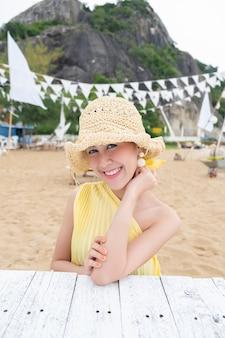 山の海辺でカジュアルな身に着けている麦わら帽子の美しいアジアの女性の肖像画。