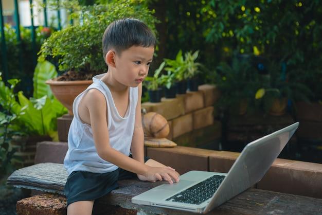 庭に座っているアジアの男の子の子供とラップトップを使用して教育またはゲームをプレイします。