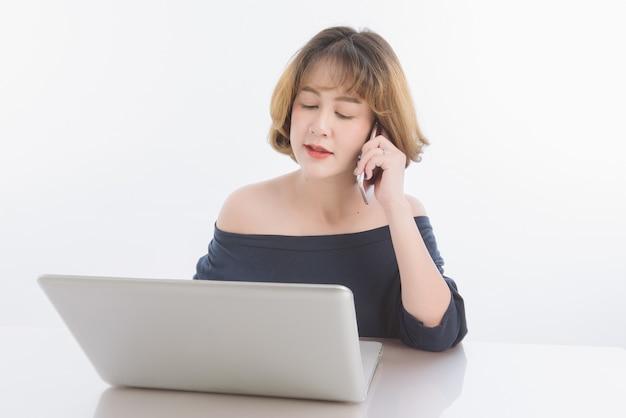 Молодая азиатская женщина дела сняла волосы работая и говоря телефон на столе офиса на белизне