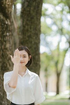アジアの女性のスタンドの肖像画は、彼女の手と公園で笑顔で目を閉じます。