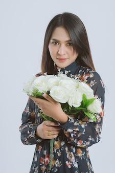 花の花束を保持している若いアジア女性の肖像画