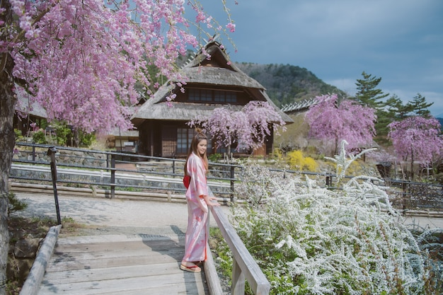 日本の桜と伝統的な日本の着物を着ているアジアの女性。