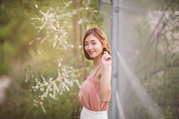 Портрет азиатской женщины усмехаясь в парке и смотря камеру. счастливый женский открытый.