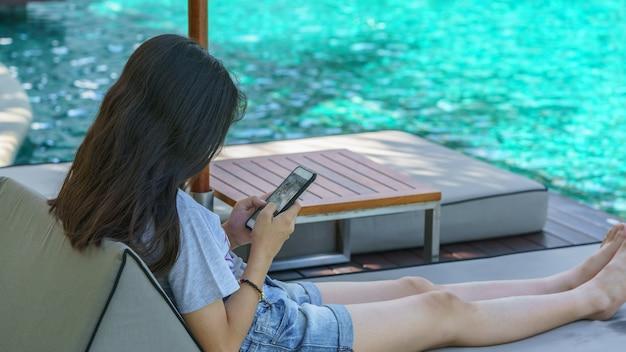 Азиатский подросток расслабляющий и играя мобильный телефон рядом с бассейном в хуа хин