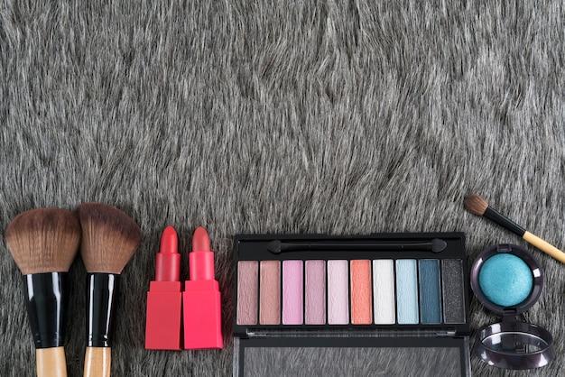 美容コンセプト:アイシャドウパレット、メークアップブラシ、灰色の偽毛皮のリップスティック