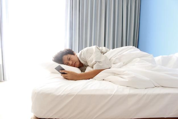 ベッドで寝てスマートフォンを持っている男