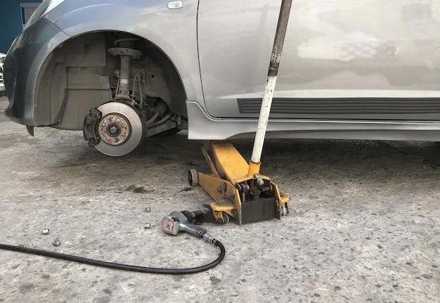 車輪のない車とジャッキ油圧で持ち上げる