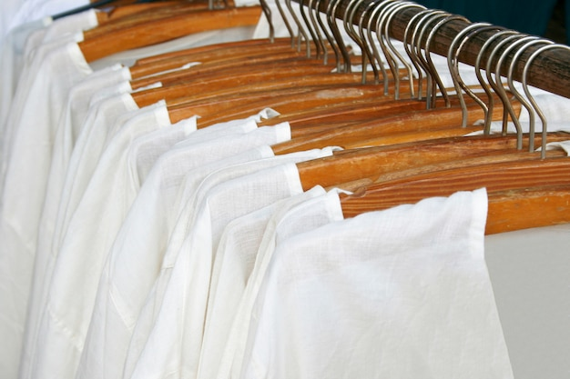 Ряд белых рубашек висит на вешалке