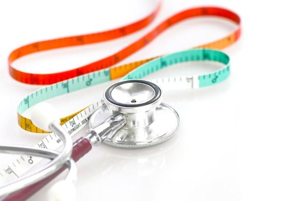 Измерительная лента и стетоскоп в концепции веса и талии.