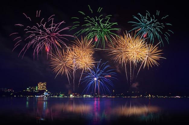 Красочное торжество фейерверков и ночник города освещают с сумерк предпосылкой неба.