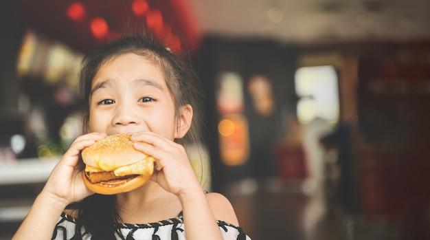 Азиатские дети едят куриный сыр гамбургский продовольственный суд