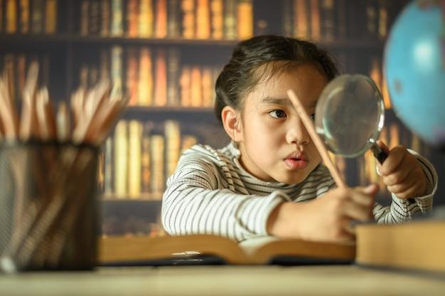 勤勉なアジアの子供女の子は室内の机に座っています。子供が家で学んでいる