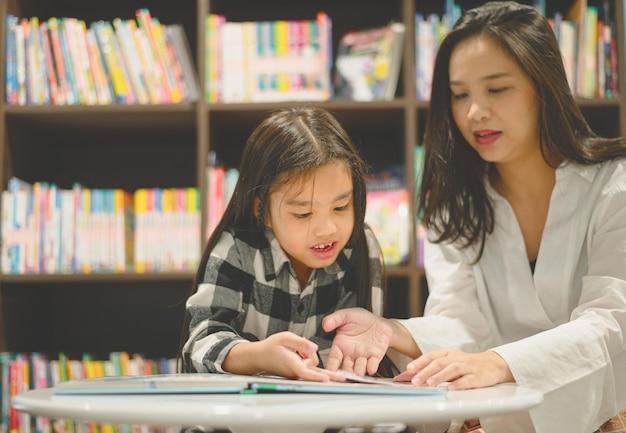 幸せな母と娘が一緒に本を読んでいます。