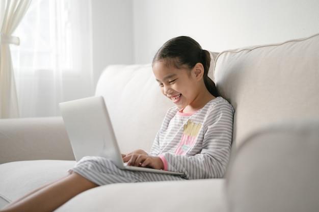 Обратно в школу, азиатка маленькая девочка с помощью своего ноутбука