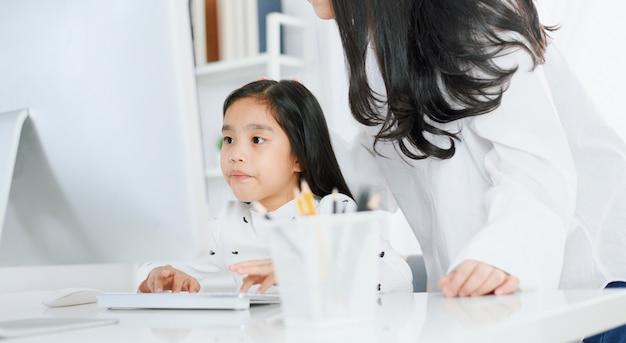 彼女の母親と一緒にコンピューターを見て幸せな少女