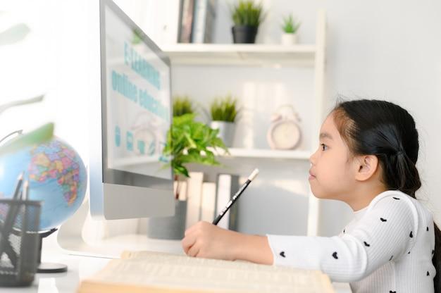 Счастливый красивый студент маленькой девочки, использующий компьютер, чтобы учиться через электронное обучение онлайн