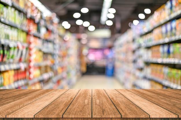 スーパーマーケットの空の上の木製のテーブルは、背景をぼかし