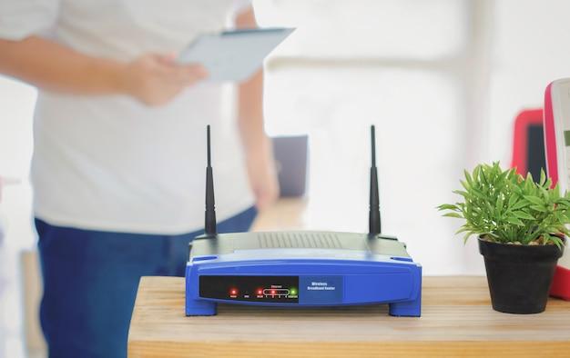 ワイヤレスルーターと自宅のオフィスのリビングルームでスマートフォンを使用している人、自宅で作業するための機器のクローズアップ