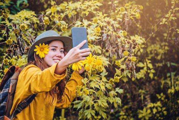 バックパックを持った女の子が電話を使って、ブアトンの花の黄色の写真を自分撮りにしています。