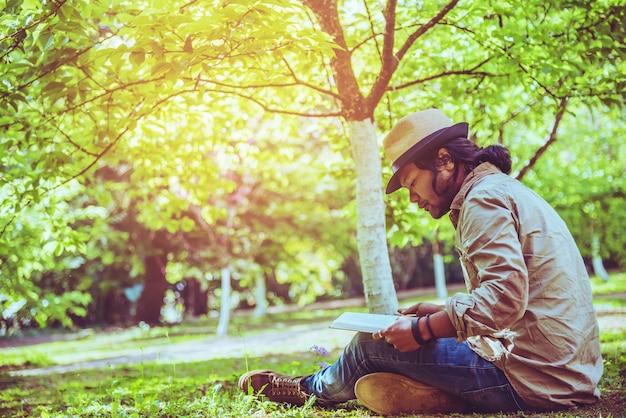 アジア人の旅行自然。トラベルリラックス。睡眠リーディングブックパークの芝生で。夏に。
