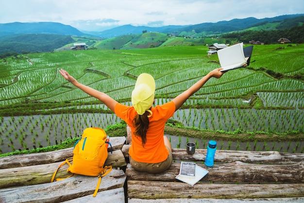 アジア人女性旅行自然。トラベルリラックス。立っている読書本家のバルコニー。夏に。