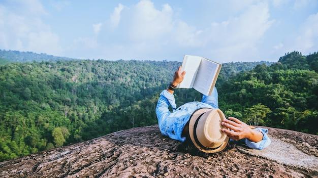 アジア人旅行は休日にリラックスします。睡眠は岩の崖の読書をリラックスさせる。夏の夏