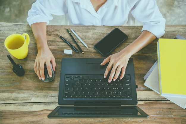 座っている女性のラップトップで木のテーブルでの作業