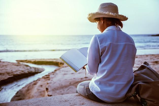 アジアの女性がビーチで読書