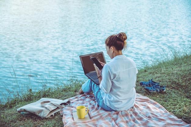 川の隣に座っている女性
