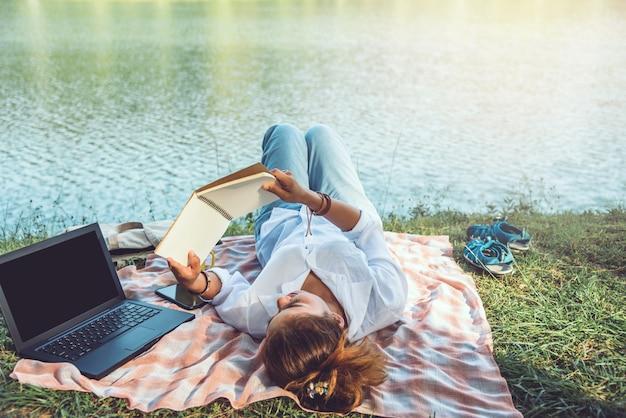 川の横にある女性の読書