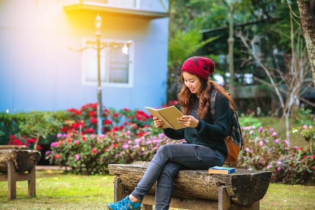 女の子は微笑んで、読んだ本に満足していました。フラワーガーデンで本を読みます。