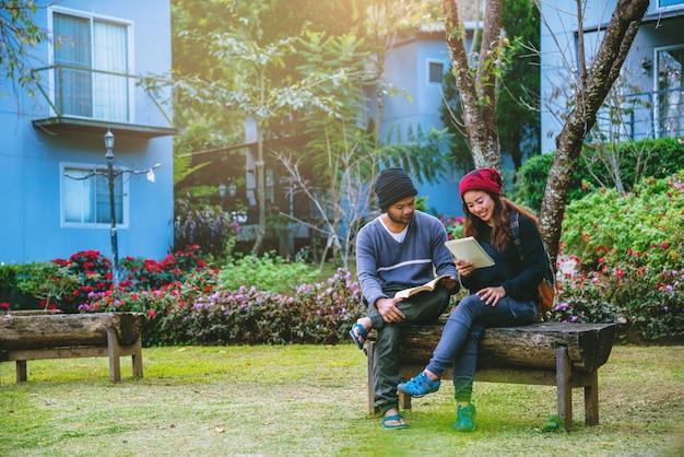 アジアのカップルは微笑んで、読んだ本に満足していました。美しい花畑の中で、バレンタイン