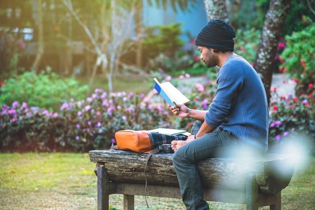 若い男は公園で本を読んでいた。自然の木々と美しい花の庭の中で