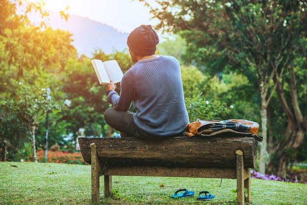 若い男は山で自然を旅し、座ってリラックスし、花の庭で本を読んでいます。