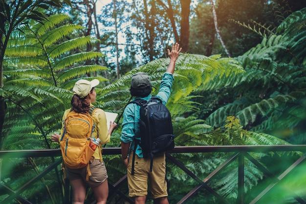 Азиатская пара путешествия природа прогулки расслабиться и изучать природу в переднем плане.