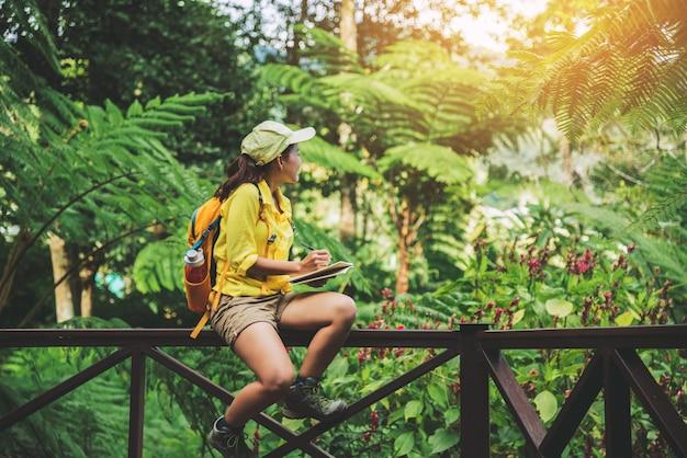 Молодая женщина, которая сидит, пишет, записывает и изучает природу леса.