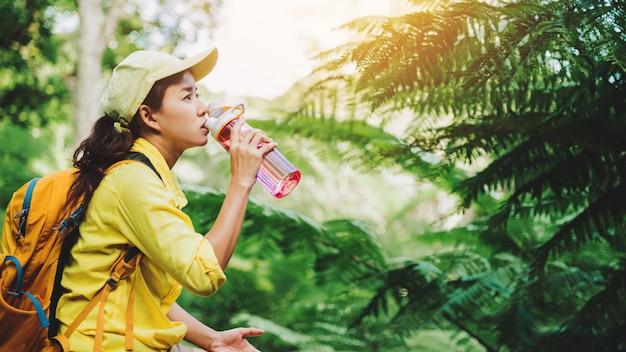 Молодая женщина путешествует, записывает и изучает природу леса. она сидит, отдыхает и пьет воду.