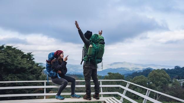アジアのカップルは冬に山の自然を旅行します。