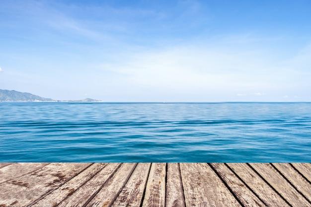 海と青空の背景に木製の通路
