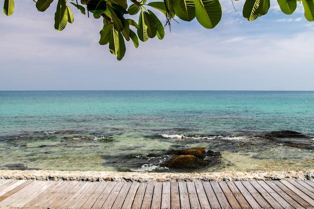 歩道の木は青い空夏の背景と海のビーチで遊歩道を橋します。