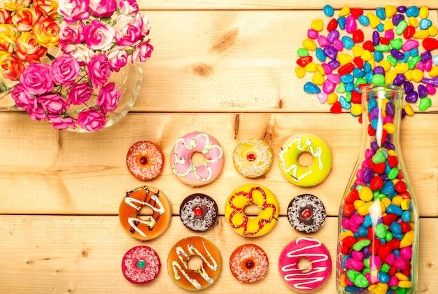 Сладкие пончики пастельного цвета с розовым цветком на деревянном фоне