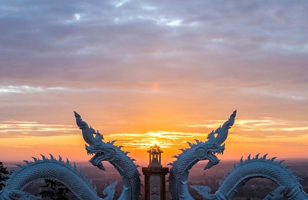 ナガ族または蛇の像と日の出背景、タイ