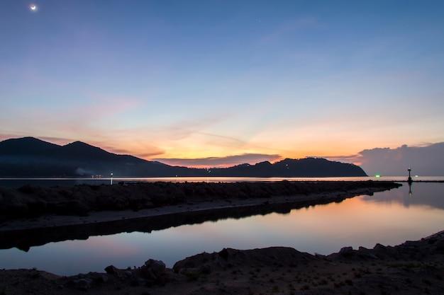 夕日とビーチの漁師と背景