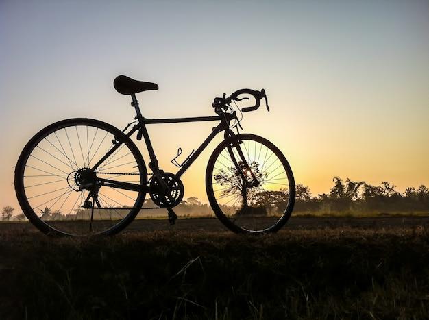 シルエットの朝の光とヴィンテージの田舎のわらの風景に自転車