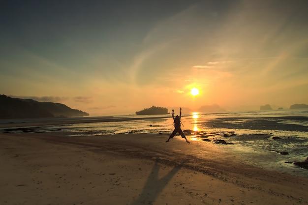 シルエット男とビーチでの夕日夏の日に楽しんで休暇休暇