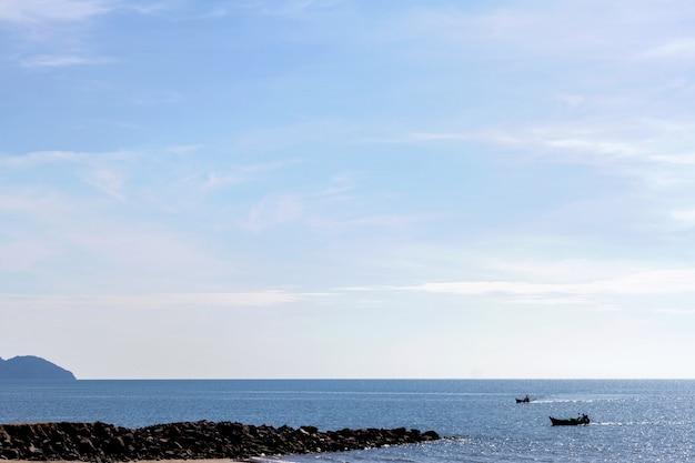 夏の朝に海とビーチで漁船
