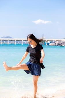 ビーチで美しい女性の肖像画。彼女は幸せで笑顔です。リラックスしているように見え、太陽と海が彼女の後ろにいて休暇中にいることができる