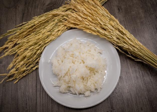 灰色の木製の背景と乾燥した水田米、米植物の白い皿の中の米
