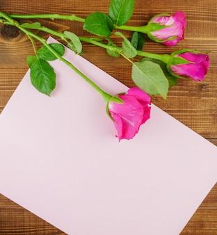 ベージュの木製の背景にピンクのバラ